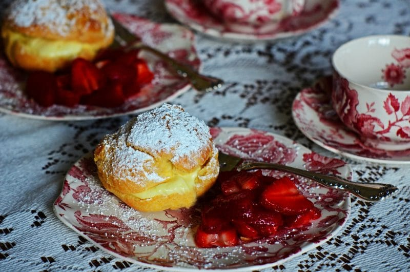 Cream puff with strawberries on a pink and white vintage plate