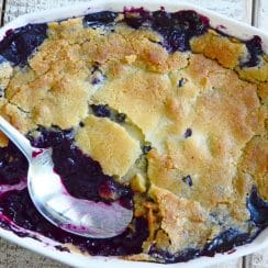 Blueberry cobbler with golden top and a spoon on a white wood table, Maureen ABood