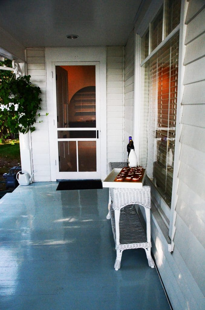 Front door to the house on the Bluff with gray painted porch floor and wicker furniture, Maureen Abood