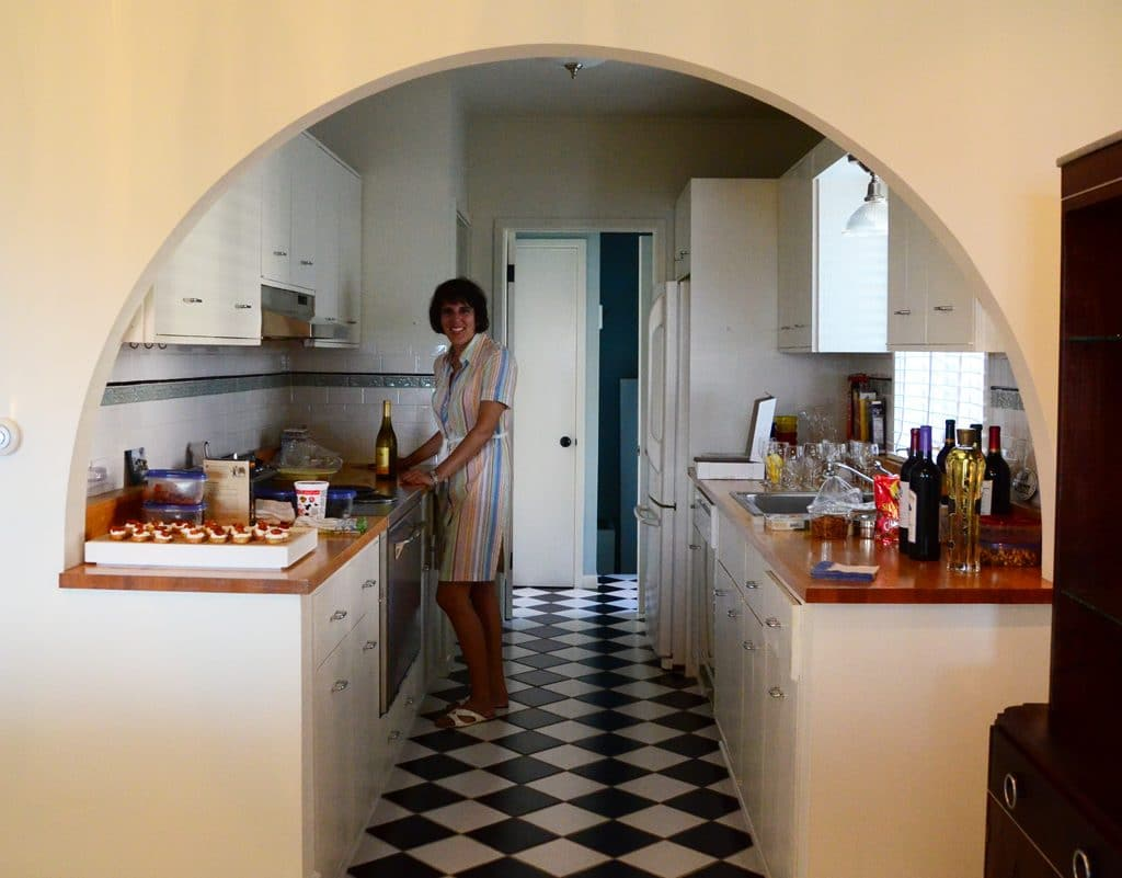 Peggy in the kitchen under a curved doorway with checkerboard floor, Maureen Abood