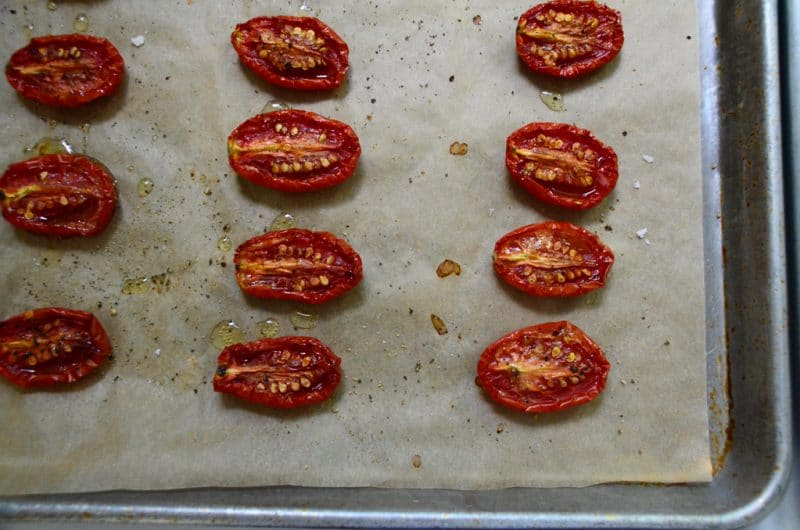 Roasted cherry tomato halves on a parchment lined sheet pan, Maureen Abood