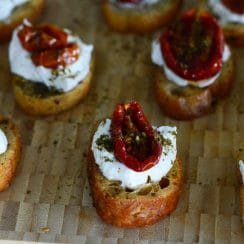 Za'atar roasted tomatos with labneh on crostini, displayed on a cutting board, Maureen Abood