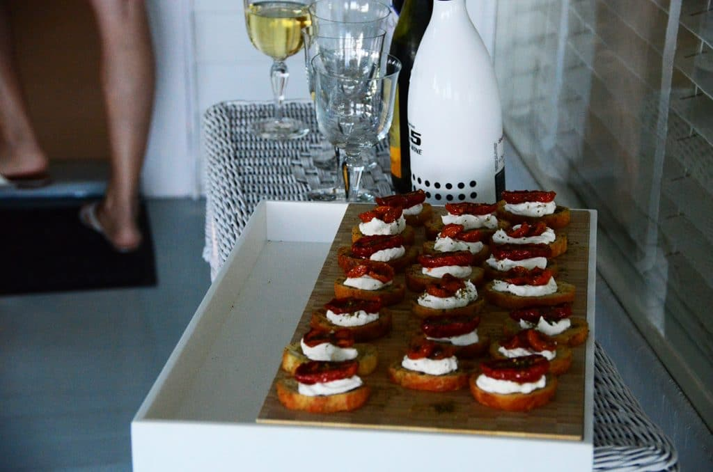 A wicker sideboard with za'atar roasted tomatoes and labneh on crostini, served on a cutting board and surrounded by champagne glasses, Maureen Abood