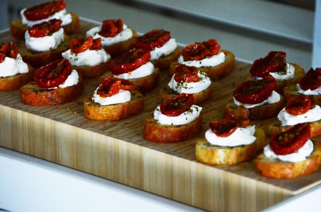 Za'atar roasted tomato crostini with labneh on a wooden board, Maureen Abood