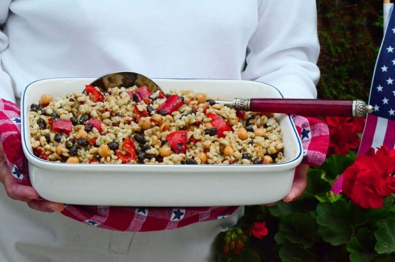 Square dish with barley picnic salad and a big spoon, in Mom's hands