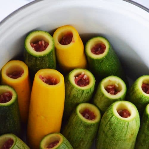 Yellow and green zucchini squash stuffed with meat and rice, lined up in a big white pot.