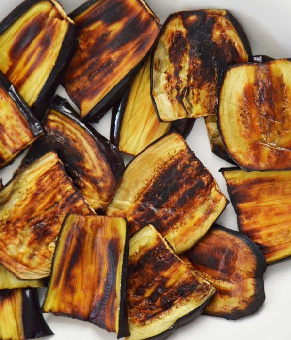 Darkly broiled eggplant on a white dish with blue rim