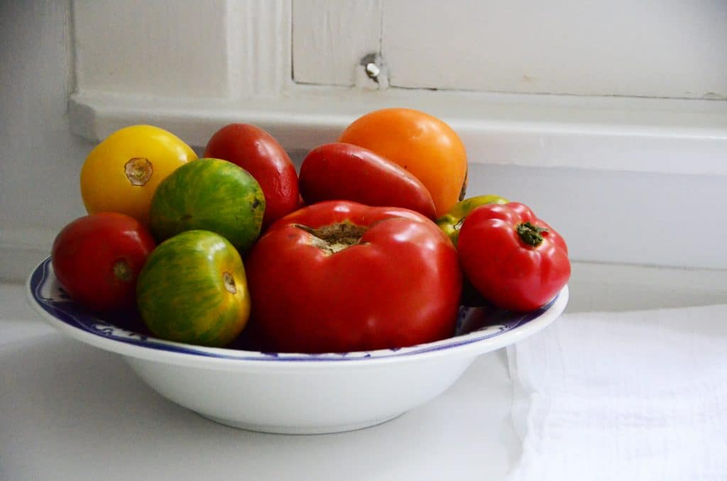 Bowl of red, yellow, and green tomatoes on the white kitchen counter, Maureen Abood