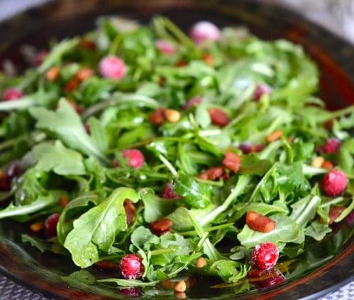 Arugula with sugared cranberries on a platter