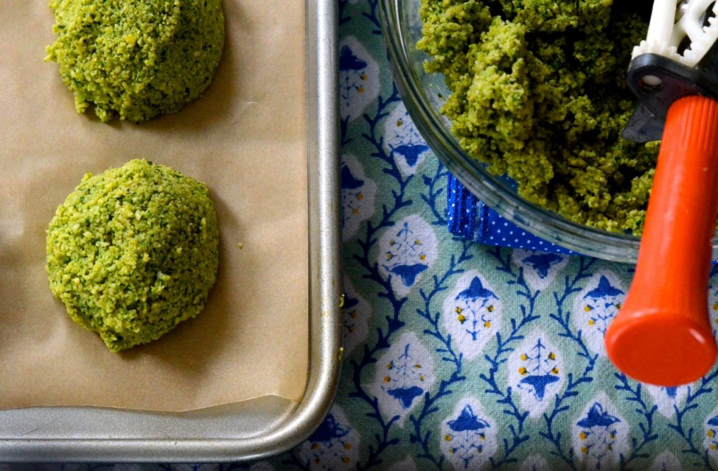 Homemade falafel is bright green with a mix of fresh herbs, scooped onto a sheet pan and ready to fry.