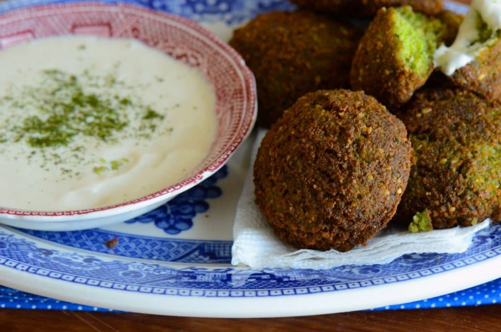 Homemade Fresh Herb Falafel is ready to eat with tahini yogurt sauce, on a lovely blue plate.