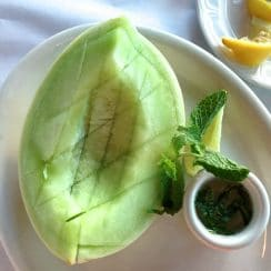 Ripe honeydew melon with a cup of fresh mint syrup and lemon wedges, on a white plate, Maureen Abood.com