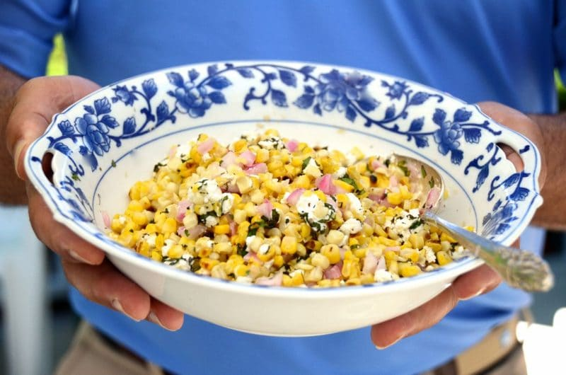 Grilled yellow corn salad with herbs and feta in a blue rimmed bowl