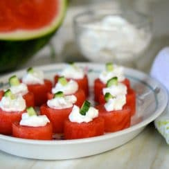 Watermelon bites with labneh and cucumber on a plate, sourrounded by watermelon and a green-trimmed towel, Maureen abood