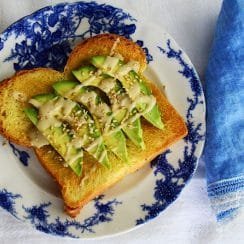 Salted Tahini Avocado Toast on a blue floral plate with blue linen napkin.
