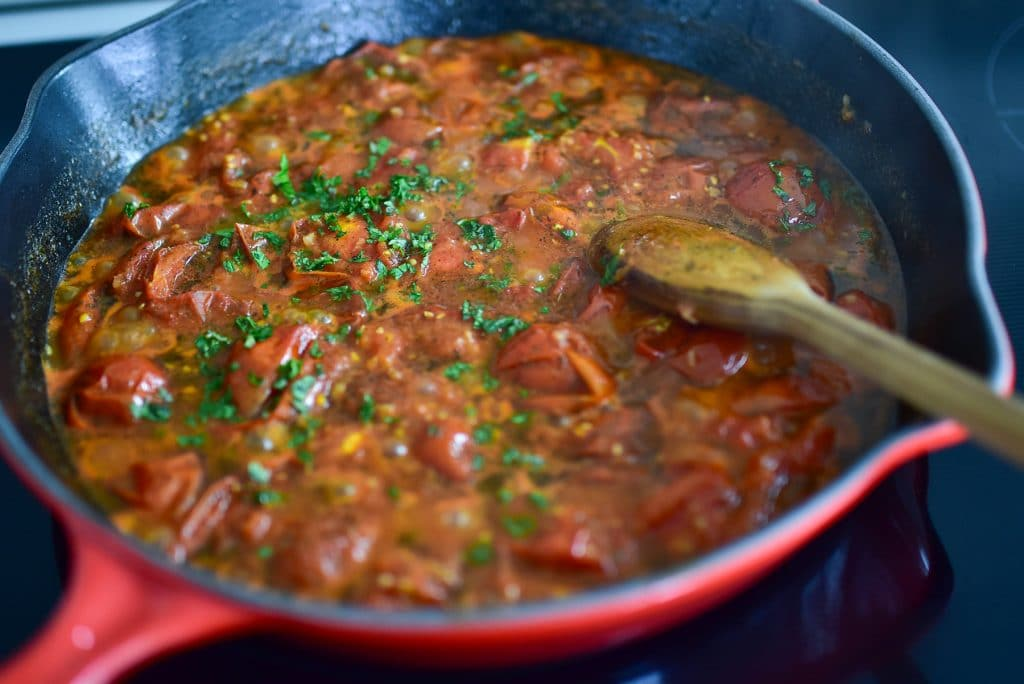 Tomatoes in a red saute pan with chopped fresh herbs, stirred with a wooden spoon