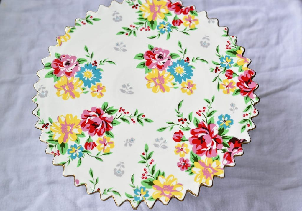 Pedestal cake plate decorated with painted roses in pink, blue, yellow and green