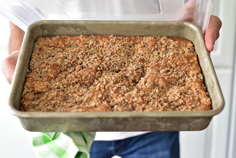 Rhubarb cake in a 13x9x2-inch pan, in Dan's hands with a green gingham napkin.