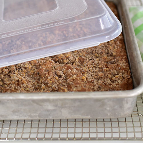 Rhubarb cake in a 13x9x2-inch pan with a lid, on a cooling rack with a green gingham napkin.