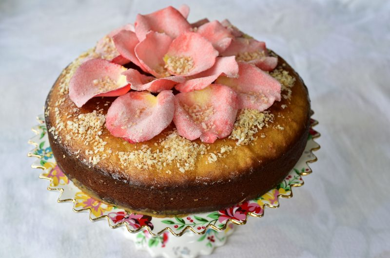 A semolina cake topped with sugared rose petals, sitting on a pedestal cake plate.