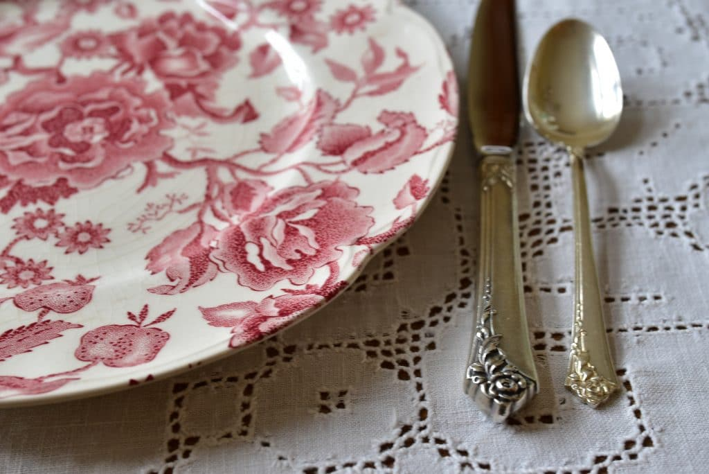 Sterling silver with a rose pattern and rose chintz china plate on a cream hemstitched tablecloth