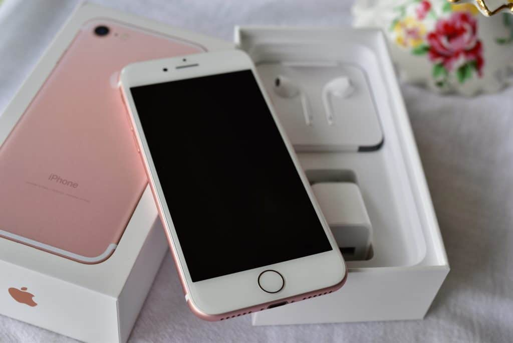 Rose colored iPhone with its box and earbuds