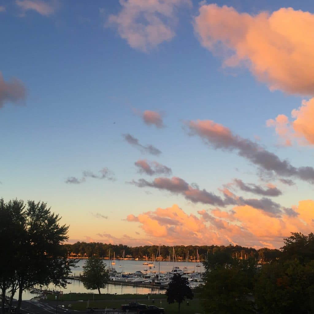 Sunrise over Little Traverse Bay, with pink clouds against a deep blue morning sky
