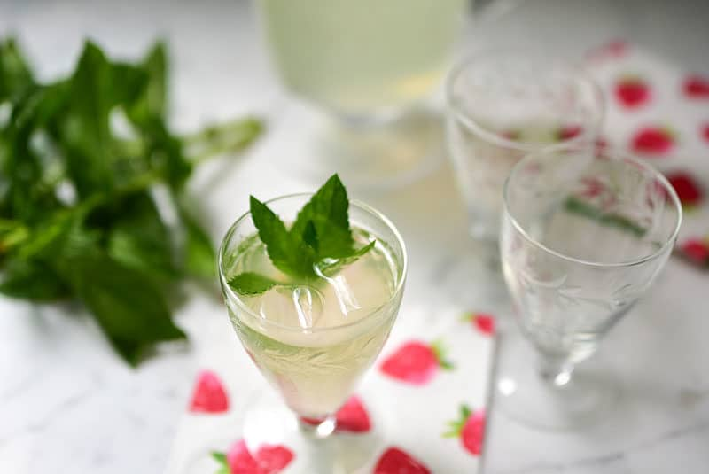 Fresh mint lemonade with fresh mint sprigs in small glasses on a strawberry printed napkin, Maureen Abood.com