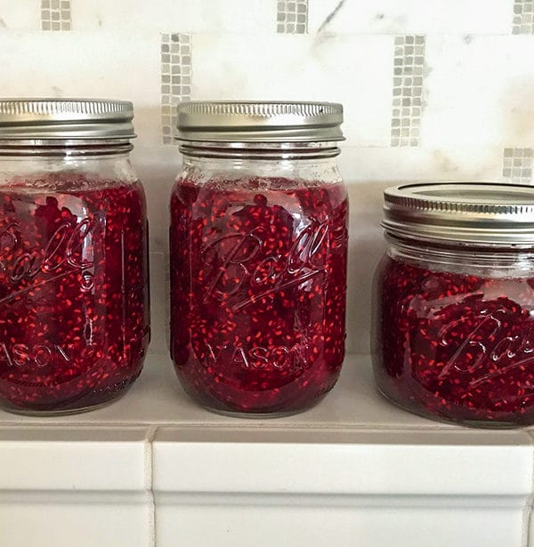 Simple Raspberry Jam in Ball jars on a tile kitchen shelf, Maureen Abood