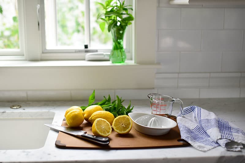 Lemons cut for juicing on a board with a knife and towel underneath the window, Maureen Abood.com