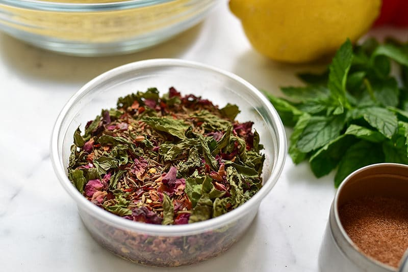 Dried mint and rose petals in kibbeh spice in a plastic container, surrounded by fresh mint and lemon, Muareen Abood
