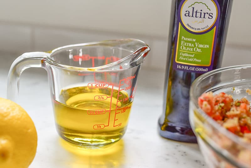 Olive oil in a glass measuring cup with a bottle next to it, Maureen Abood