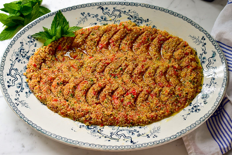 Tomato kibbeh on a blue and white oval platter, garnished with fresh mint, Maureen Abood.
