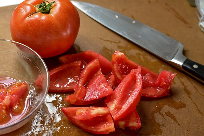 Seeded tomatoes on a cutting board with a sharp knife, Maureen Abood