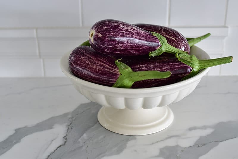 Purple eggplant in a footed dish on a marble countertop, Maureen Abood