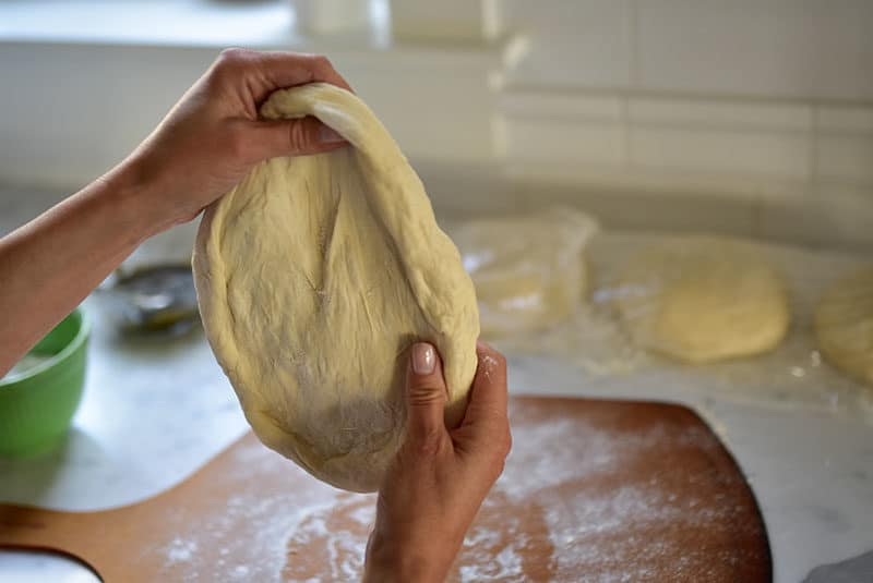 Shaping pizza dough for zaatar flatbread
