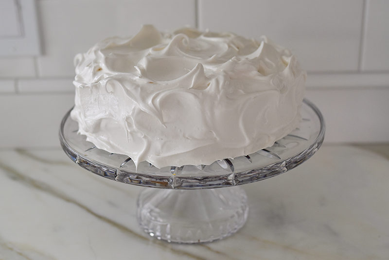 Meringue frosted cake on a crystal stand, Maureen Abood