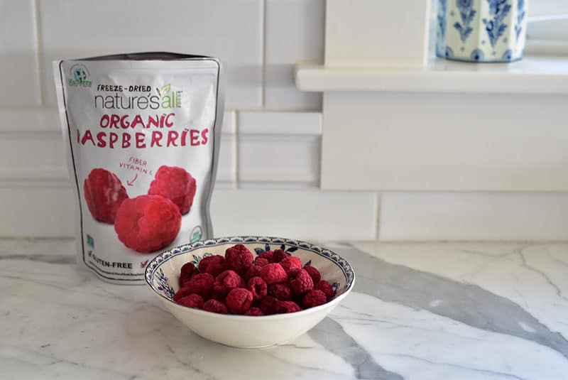 Freeze-dried raspberries in their bag and a blue bowl on the counter