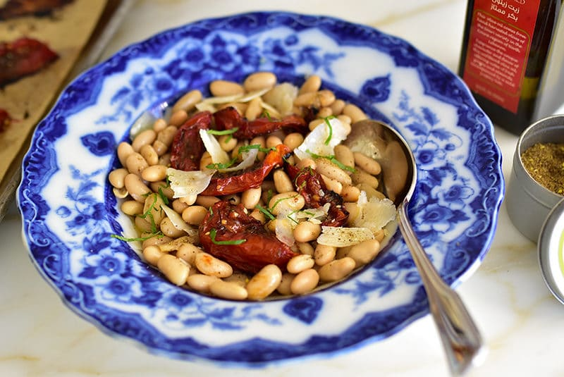 White beans with za'atar roasted tomatoes and olive oil, in a vintage blue pasta bowl