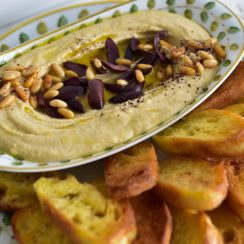 Hummus with olives, pine nuts, and crostini