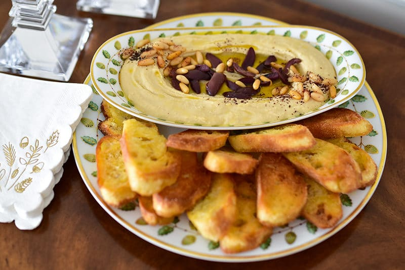 Hummus with olives in Bernardaud china, in the dining room