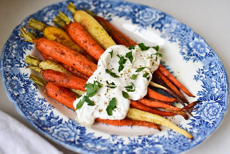 Za'atar roasted carrots with labneh on a blue floral platter