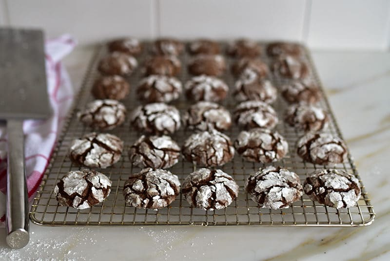 Chocolate crinkle cookies with orange blossom cooling on a rack