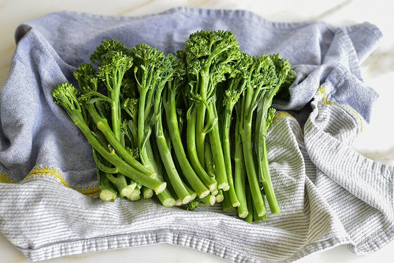Broccolini drying in a blue towel