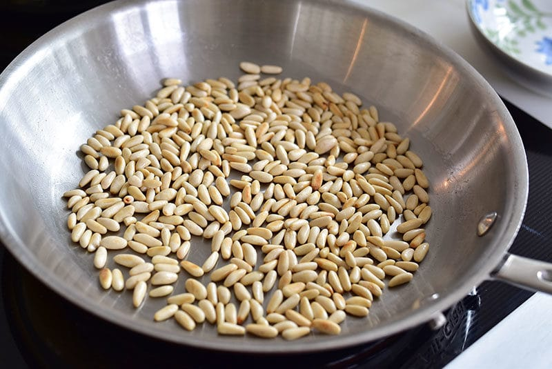 Pine nuts toasting in a dry pan