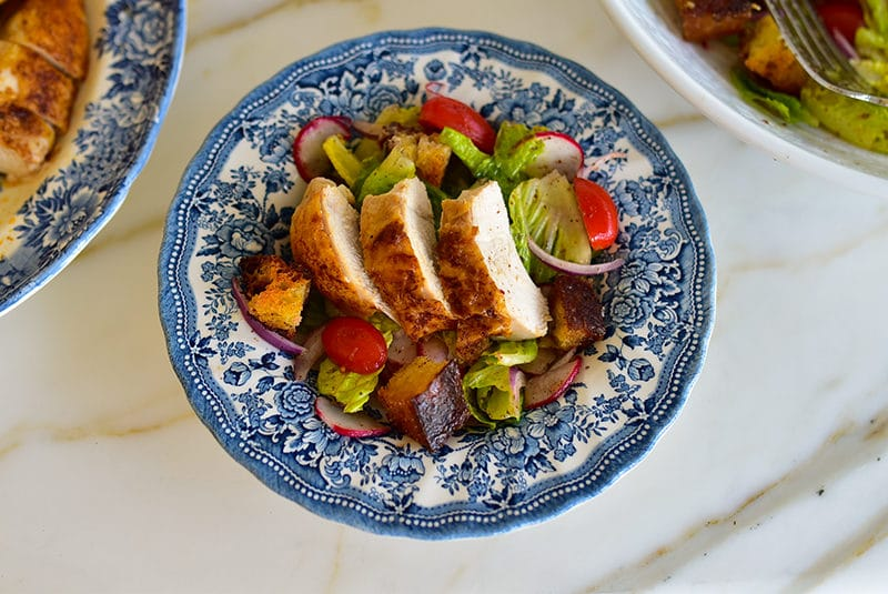 Fattoush topped with roasted chicken and croutons