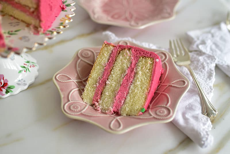 Slice of raspberry buttercream cake on a pink Juliska plate