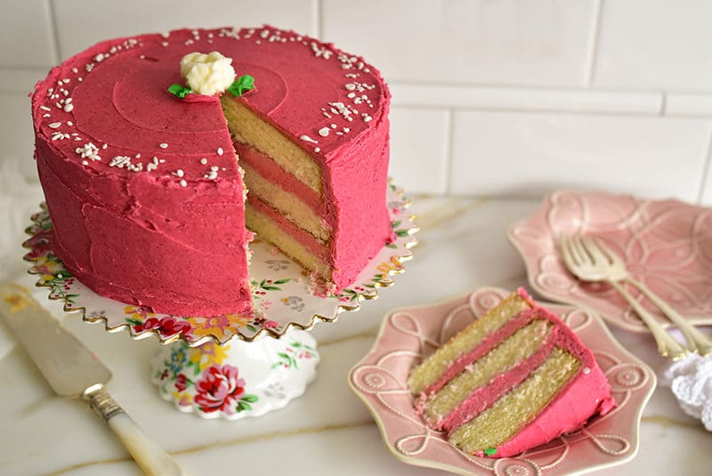 Raspberry buttercream cake with big slice cut out