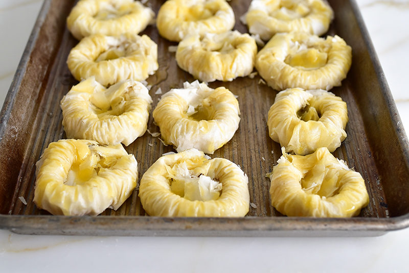 Buttered phyllo nests on a sheet pan before baking