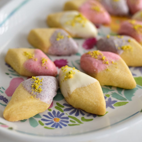 Shortbread dipped in white chocolate on a platter